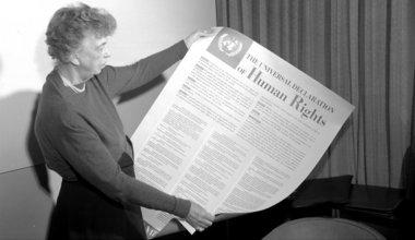 Eleanor Roosevelt des Etats-Unis tenant une affiche représentant la Déclaration universelle des droits de l'homme en anglais. (Novembre 1949). Photo ONU