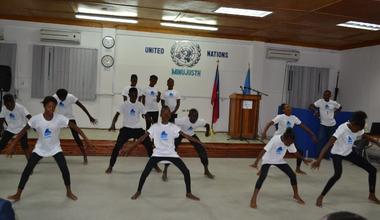 Pour la Journée des Casques bleus, les policiers internationaux de la MINUJUSTH ont célébré la richesse et la diversité des cultures traditionnelles avec de jeunes danseurs haïtiens en partageant des danses haïtiennes, indiennes et népalaises. © UNPOL Comlan Flavien Dovonou / UN / MINUJUSTH, 2018