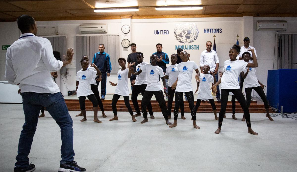 Pour la Journée des Casques bleus, les policiers internationaux de la MINUJUSTH ont célébré la richesse et la diversité des cultures traditionnelles avec de jeunes danseurs haïtiens en partageant des danses haïtiennes, indiennes et népalaises. © Leonora Baumann / UN / MINUJUSTH, 2018