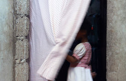 Women and children are disproportionately affected. According to the Office of the UN High Commissioner for Refugees (UNHCR), young girls are the most demanded and profitable prey for traffickers. Above, a child stands in a curtained doorway in Yemen. UNHCR/Rocco Nuri